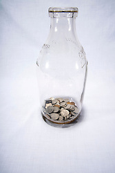 United States coins saved in a clear glass milk jug or jar