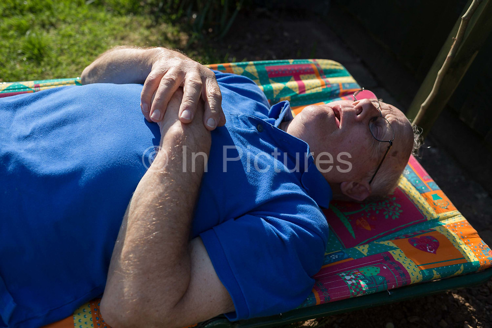 An elderly man in his eighties sleeps horizontally in spring sunshine, on a sun lounger in his rear garden on 21st April 2019, in Nailsea, North Somerset, England.