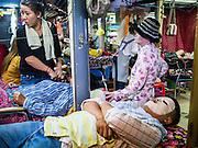 02 FEBRUARY 2013 - PHNOM PENH, CAMBODIA: A man gets a facial at a beauty parlor in a market in Phnom Penh, Cambodia.       PHOTO BY JACK KURTZ