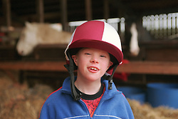Young boy with Downs syndrome wearing riding hat,