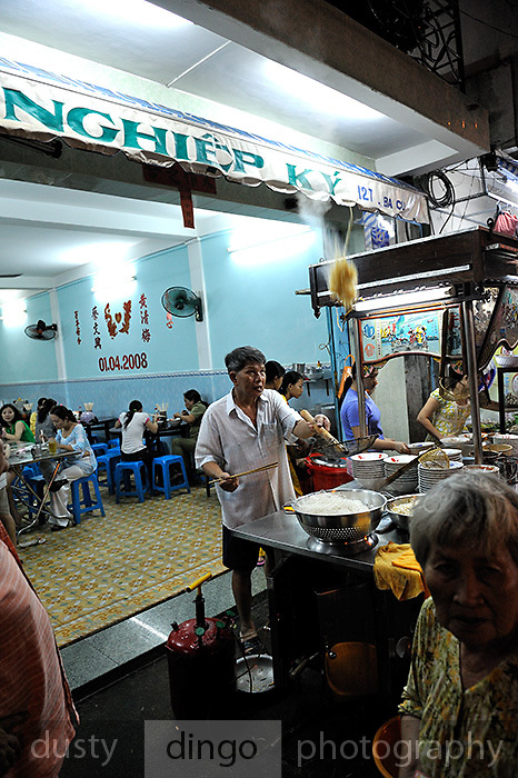 Cooking on pavement outside his noodle restaurant, the cook catches a serve of noodles he had just thrown up into the air. Vung Tau, Vietnam