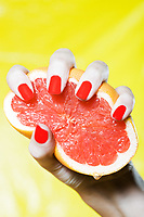 woman hand squeezing grapefruit studio on yellow background