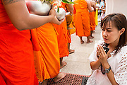 """22 JULY 2013 - PHRA PHUTTHABAT, THAILAND: A woman prays as monks past her during the Tak Bat Dok Mai at Wat Phra Phutthabat in Saraburi province of Thailand, Monday, July 22. Wat Phra Phutthabat is famous for the way it marks the beginning of Vassa, the three-month annual retreat observed by Theravada monks and nuns. The temple is highly revered in Thailand because it houses a footstep of the Buddha. On the first day of Vassa (or Buddhist Lent) people come to the temple to """"make merit"""" and present the monks there with dancing lady ginger flowers, which only bloom in the weeks leading up Vassa. They also present monks with candles and wash their feet. During Vassa, monks and nuns remain inside monasteries and temple grounds, devoting their time to intensive meditation and study. Laypeople support the monastic sangha by bringing food, candles and other offerings to temples. Laypeople also often observe Vassa by giving up something, such as smoking or eating meat. For this reason, westerners sometimes call Vassa the """"Buddhist Lent.""""     PHOTO BY JACK KURTZ"""