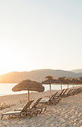 View of beach with sun loungers at sunset, Ajaccio, Corsica, France