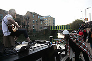 A woman pays a busker playing to a large crowd on Regents Canal by tapping her card during the second coronavirus national lockdown on November 7th 2020 Hackney, East London, United Kingdom. The busker playing on the roof top of a canal boat draws a large crowd enjoying his music in-spite of current social distance rules. He stopped playing before getting into trouble with the police which did eventually break up the crowd. The UK Government introduced a 4 week lockdown from November 5th - December 2nd to combat the coronavirus outbreak. It is the third day of the national lockdown and restrictions mean that people are only allowed to meet outside, in pairs and only if keeping social distance. Only if they already live together or have formed a social bubble can they interact freely.