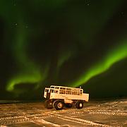 Aurora borealis, or northern lights, dance above a Tundra Buggy vehicle at Cape Churchill, Manitoba, Canada.