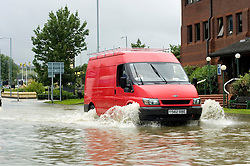 A red Ford Pannel van drives through the flooding on The Common Ecclesfield Sheffield South Yorkshire.25 June 2007.Image COPYRIGHT Paul David Drabble.