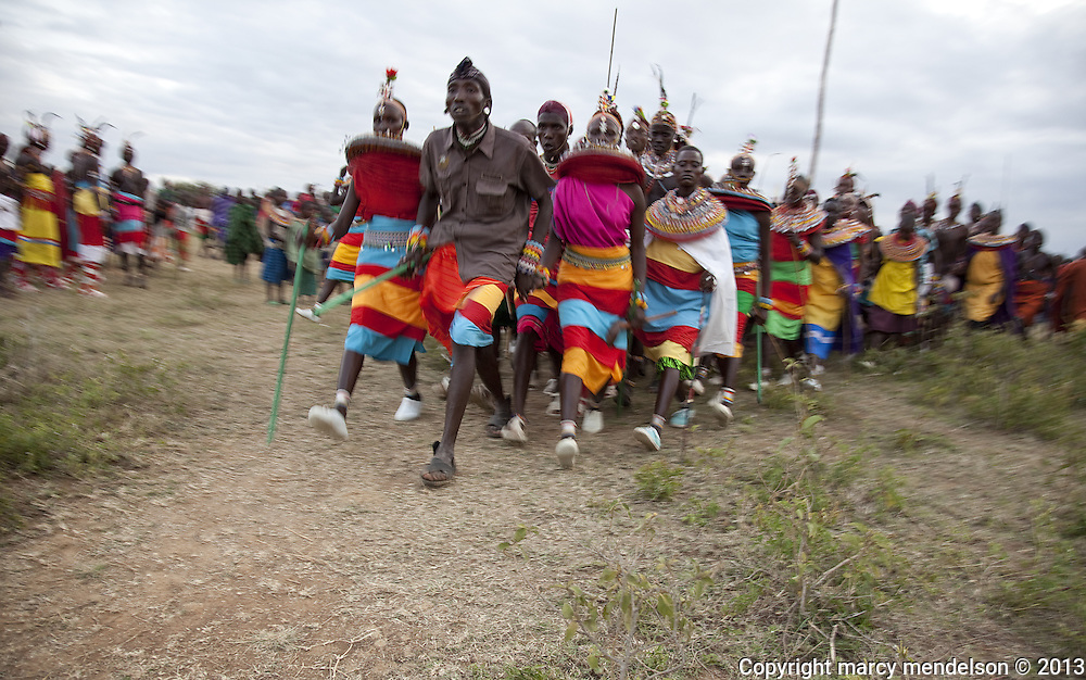 Morans & young women celebrate with dancing and singing into the night.  Pictured here is the partner dance called Maasani.  Outside Kisima, Samburu County, Kenya.  August 22, 2013.