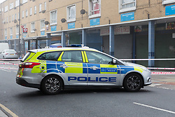 © Licensed to London News Pictures. 03/04/2017. LONDON, UK.  A police car at the crime scene and police cordon around BJ Wines and parade of shops in Freemasons Road, Canning Town, east London. Ahmed Jah, 21 is reported to have been knifed inside the off license, BJ Wines in Freemasons Road yesterday afternoon after he was set upon by a gang of men and stabbed in the chest. Emergency ambulance services attended and the man was pronounced dead at the scene shortly after.  Photo credit: Vickie Flores/LNP