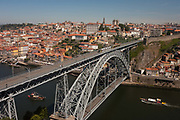 A morning aerial panorama of boats about to pass under, while a tram crosses over the Ponte de Dom Luis I bridge with the city of Porto behind on the River Douro and a foreground of warehouse rooftops, on 20th July, in Porto, Portugal. The Dom Luís I or Luiz I Bridge is a double-decked metal arch bridge that spans the Douro River between the cities of Porto and Vila Nova de Gaia in Portugal. At the time of construction its span of 172 m was the longest of its type in the world.