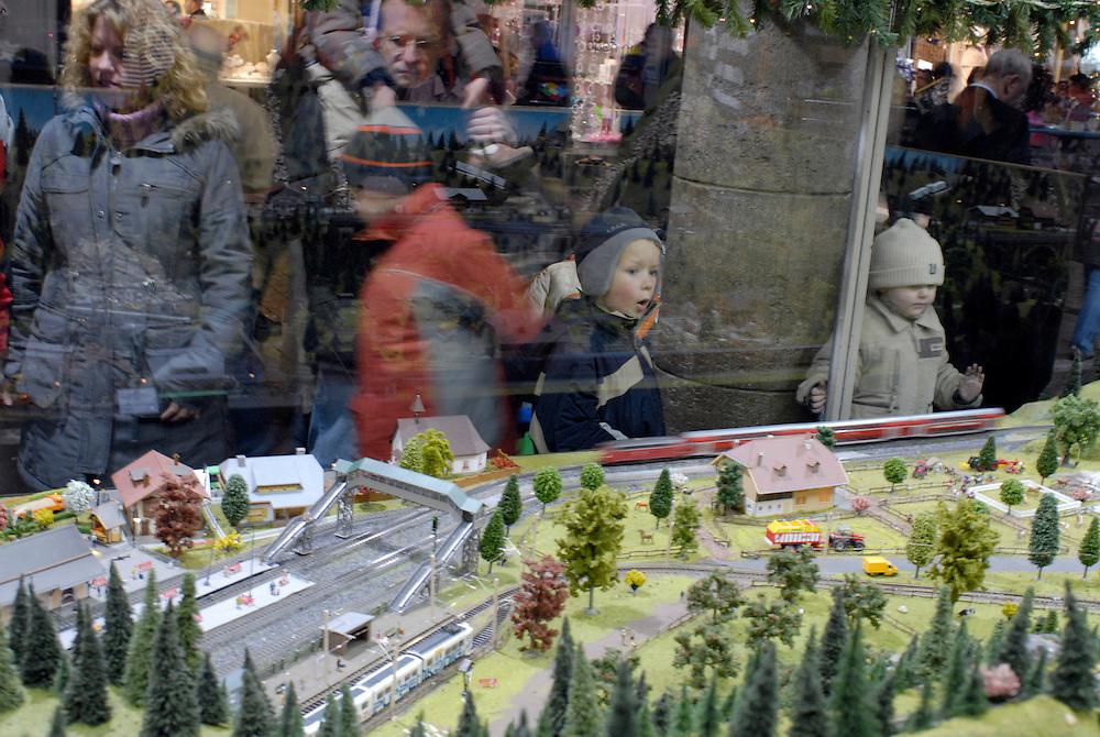 Deutschland, NRW,Bonn,   Kinder staunen am Schaufenster eines Spielwarenladens vor einer Eisenbahnlandschaft |  Children and adults glancing surprised at a toy railway landscape at a store in Bonn, Germany   |