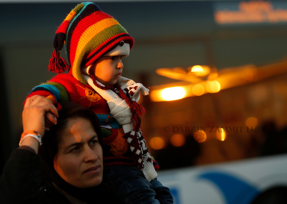 A migrant carries a baby on her shoulders after refugees and migrants arrived on the passenger ferry Blue Star1 at the port of Piraeus, near Athens, Greece, January 31, 2016. Photo: Darrin Zammit Lupi