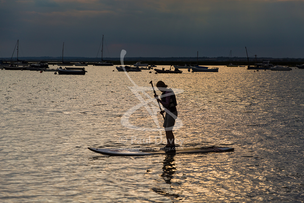 A stand-up paddler makes her way across the sunlit water in the early evening at West Mersea, Mersea Island, near Colchester in Essex. West Mersea, Essex, July 11 2019.