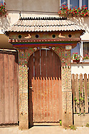 Traditional wooden Székely ( Szekely ) gates in a Szekely village near Cluj, Eastern Transylvania. Carved with folk art & painted the Szekely gate also has dove cotes above the gate. .<br /> <br /> Visit our ROMANIA HISTORIC PLACXES PHOTO COLLECTIONS for more photos to download or buy as wall art prints https://funkystock.photoshelter.com/gallery-collection/Pictures-Images-of-Romania-Photos-of-Romanian-Historic-Landmark-Sites/C00001TITiQwAdS8