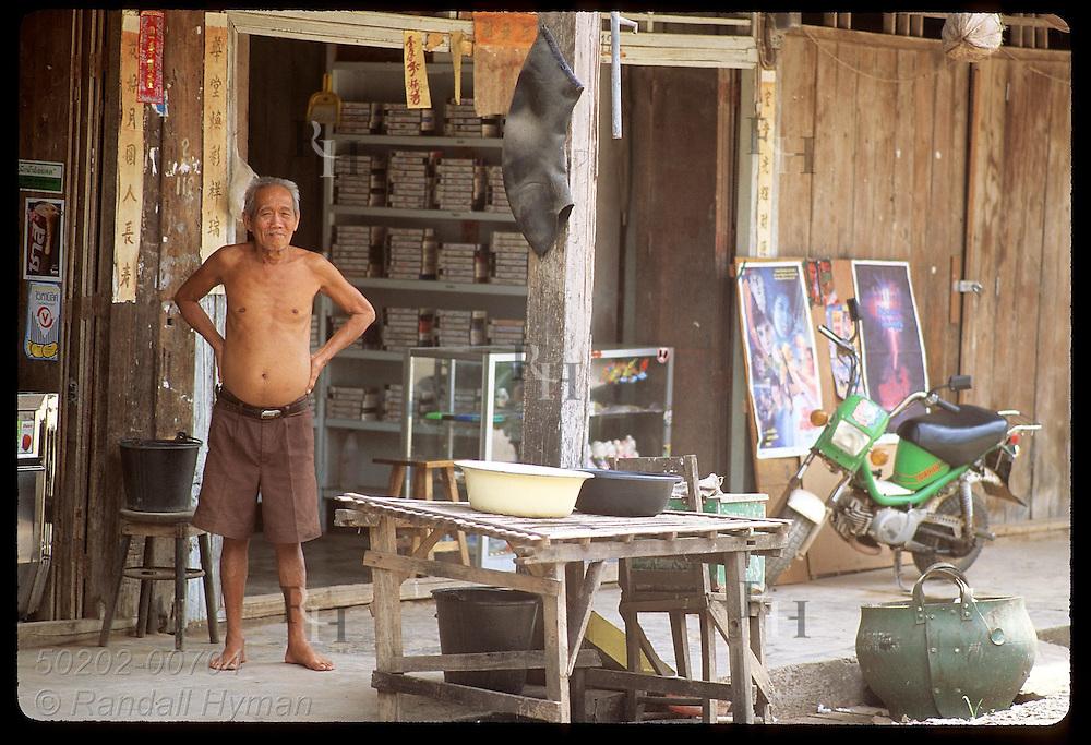 Merchant stands at door of modest video rental store in quiet side street of downtown Krabi. Thailand