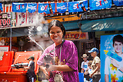 "13 APRIL 2013 - BANGKOK, THAILAND:  A Thai woman squirts a foreign tourist with water on Khao San Road, which is Bangkok's ""backpacker"" district, during Songkran celebrations in the Thai capital. Songkran is celebrated in Thailand as the traditional New Year's Day from 13 to 16 April. The date of the festival was originally set by astrological calculation, but it is now fixed. If the days fall on a weekend, the missed days are taken on the weekdays immediately following. Songkran is in the hottest time of the year in Thailand, at the end of the dry season and provides an excuse for people to cool off in friendly water fights that take place throughout the country. Songkran has been a national holiday since 1940, when Thailand moved the first day of the year to January 1.   PHOTO BY JACK KURTZ"