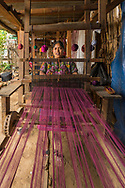 Finally the woman can start weaving. Depending on the length of the piece, they can spend up to three weeks weaving a single textile.