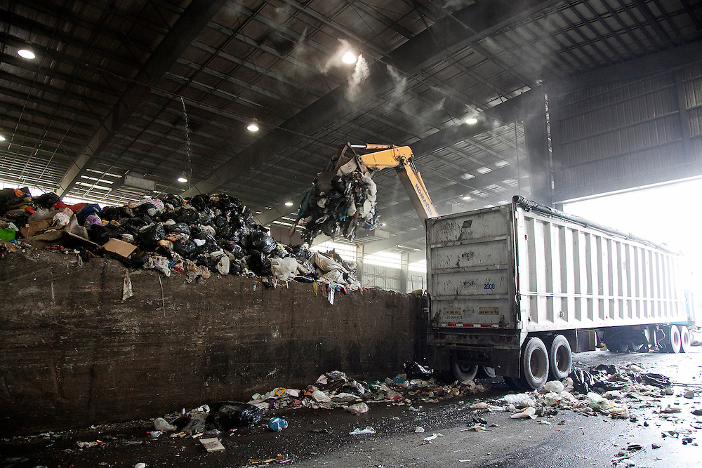 Track-hoe Claw at waste transfer station loads solid municipal waste into highway transfer truck bound for landfill