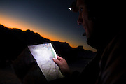 Climber Obadiah Reid navigates at night by reading a map by headlamp, North Cascades National Park, Washington.