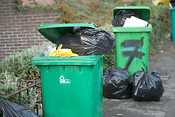 Bulging green wheelie bins and rubbish bags in the street waiting for collection,