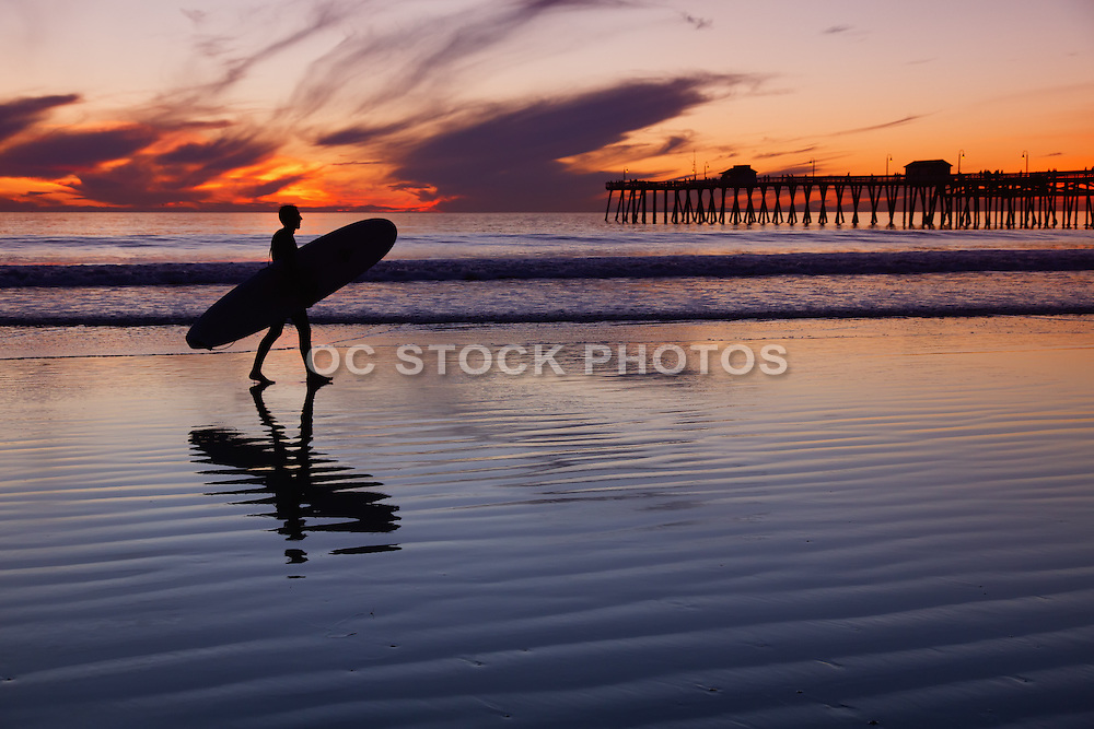 Surfer Walking at Low Tide by the San Clemente Pier at Dusk