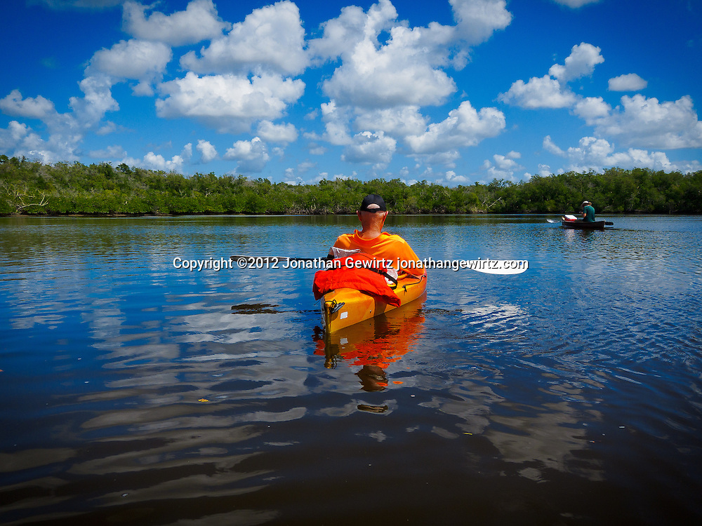 A kayaker and a canoist take a break from paddling on the Turner River in the Big Cypress section of the Florida Everglades. WATERMARKS WILL NOT APPEAR ON PRINTS OR LICENSED IMAGES.
