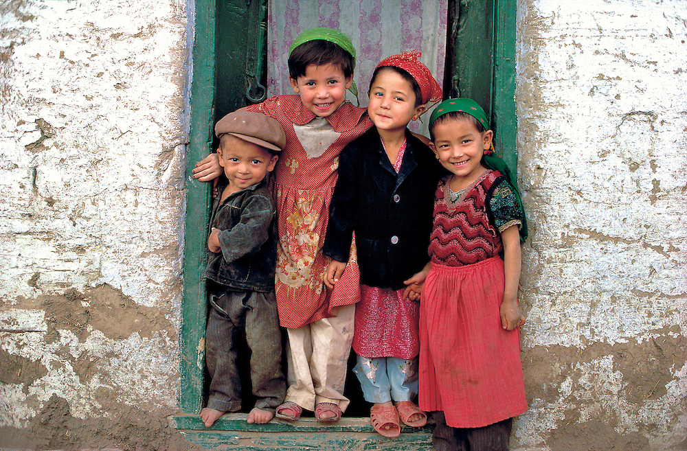 A group of Uygur children offer friendly smiles from their doorway near Kashgar, Xinjiang, China.