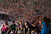 Tourists sit beneath graffiti on a wall at the entrance to the Casa di Giulietta in Verona, Italy