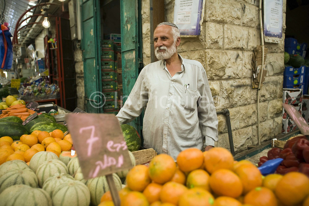 A trader on a vegetable stall at the Mahane Yahuds Market, Jerusalem, IsraelA trader on a stall at the Mahane Yahuda Market, Jerusalem, Israel