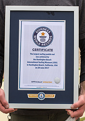 June 20, 2017 - Huntington Beach, California, USA - A surfer holds the certificate from the Guinness World Records that states that 511 surfers created the world's largest paddle out ''Surfing Circle of Honor'' in Huntington Beach Tuesday morning, June  20, 2017. (Photo by Mark Rightmire, Orange County Register/SCNG) (Credit Image: © Mark Rightmire, Mark Rightmire/The Orange County Register via ZUMA Wire)