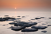 Low tide reveals numerous rows of fascinating boulders on Hunstanton's extensive beach. North Norfolk coast, East Anglia.