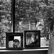 High School advanced painting intensive students use oil paints on canvas seen reflected in mirrors leaned against a window in the Dow Visual Arts Building at Interlochen Center for the Arts in Interlochen, Michigan.