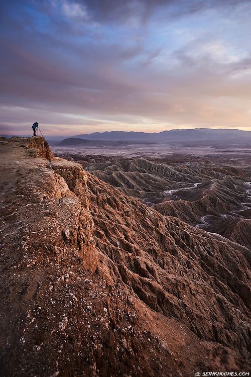 A photographer with a tripod takes a sunset photo on the precipice of Font's Point in Anza Borrego, California.