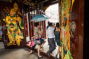 People walk through the gate at Chenghuang Miao or City God Temple in Yu Yuan Gardens bazaar Shanghai, China