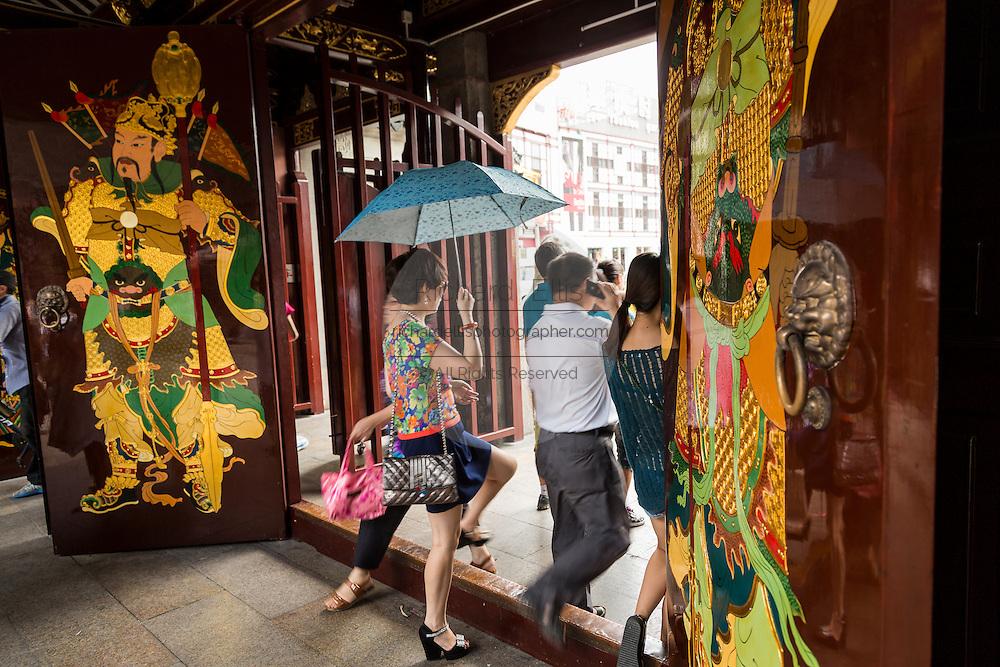 People walk through the gate at Chenghuang Miao or City God Temple in Yu Yuan Gardens bazaar Shanghai, China