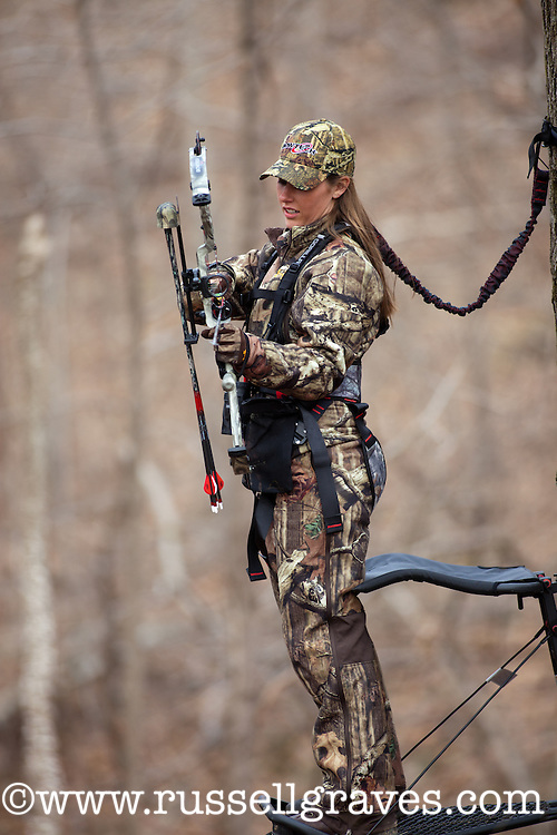 FEMALE BOWHUNTER IN A TREESTAND RATTLING FOR DEER