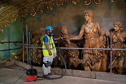 IMAGES SHOT ON APRIL 20TH 2021 © Licensed to London News Pictures. 12/05/2021. Blackpool, UK. Fibrous plasterer Ethan Brown cleans the sculptures above the stage as he works on the major conservation project taking place in the Tower Ballroom, in Blackpool, Lancashire on April 20, 2021. The Blackpool Tower Ballroom, located in the Grade 1 Listed Tower and which dates back to 1894, has undergone the most extensive programme of work and deep clean for more than 60 years totaling £1.1M. A team of skilled, specialist craftsmen, who have worked across the world on projects including the Queen's Gallery at Buckingham Palace, have dedicated more than 21,000 hours, over a period of six months, to restore the famous Ballroom to its original glory. Due to the Coronavirus pandemic the ballroom has now been closed for over 12 months and is scheduled to re-open to the public on June 21, 2021. Photo credit: Oli Scarff/LNP