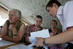 Ljudmila Datsjuk, left, is helped by a volunteer attorney, Mykola Glotov, helps Nadia Zhuk, 70, during a Òspecial consultationÓ for potential clients who are children of the Second World War, Rivne, Ukraine, June 15, 2011. This vulnerable group is made up of seniors, most of whom are not receiving proper compensation as promised by the government. The legal team advises them on how to properly fill out forms and submit them to the courthouse, while encouraging them not to give up on their rights. More than half of the worldÕs population, four billion people, live outside the rule of law, with no effective title to property, access to courts or redress for official abuse. The Open Society Justice Initiative is involved in building capacity and developing pilot programs through the use of community-based advocates and paralegals in Sierra Leone, Ukraine and Indonesia. The pilot programs, which combine education with grassroots tools to provide concrete solutions to instances of injustice, help give poor people some measure of control over their lives.