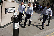 Asian city workers walk along Old Broad Street, EC2 in the City of London.