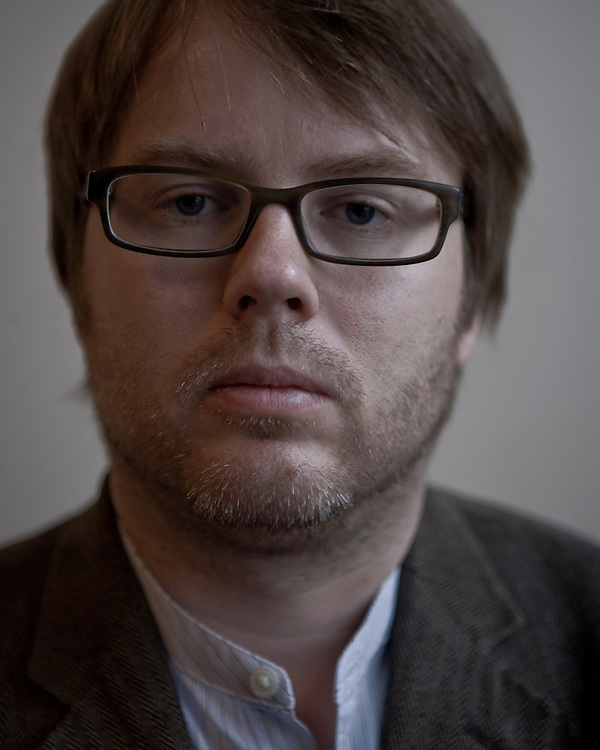 Portrat of a male with glasses and stubble looking straight ahead