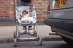 Young baby in pushchair being pushed across road near car exhaust,