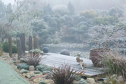 The frozen pond and deck on a frosty, foggy winter's morning. Container of Prunus incisa 'Kojo-no-mai', wooden duck ornaments and slate posts. Conifers on rock garden beyond. Design: John Massey, Ashwood Nurseries
