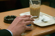 young businessman smoking and drinking coffee