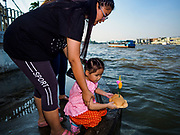 "03 NOVEMBER 2017 - BANGKOK, THAILAND: A woman and her daughter try to float a krathong in Chao Phraya River during Loi Krathong at Wat Prayurawongsawat on the Thonburi side of the Chao Phraya River. Loi Krathong is translated as ""to float (Loi) a basket (Krathong)"", and comes from the tradition of making krathong or buoyant, decorated baskets, which are then floated on a river to make merit. On the night of the full moon of the 12th lunar month (usually November), Thais launch their krathong on a river, canal or a pond, making a wish as they do so. Loi Krathong is also celebrated in other Theravada Buddhist countries like Myanmar, where it is called the Tazaungdaing Festival, and Cambodia, where it is called Bon Om Tuk.     PHOTO BY JACK KURTZ"