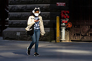 A woman wearing an oversize mask and feline ear muffs walks through the CBD. (Photo by Dave Hewison/Speed Media)
