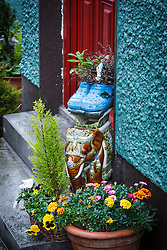 Flowers planted in pair of Crocs, with Virgin Mary statue, Kinvarra, County Galway, Ireland