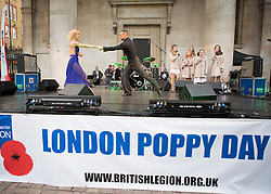 © Licensed to London News Pictures. 07/11/2013.  Strictly Come Dancing stars Robin Windsor and Aliona Vilani performed today in Covent Garden alongside the Poppy Girls as part of the Royal British Legions annual London Poppy day.  The dance stars joined service personnel to help the charity raise a million pounds in the capital today.  Photo credit: Alison Baskerville/LNP