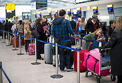 © Licensed to London News Pictures. 23/12/2016. London, UK.  Travellers queue to check in baggage at Heathrow Airport, Terminal 5,  as the Christmas getaway begins, with stations, airports and roads expected to be very busy as people start their Christmas holidays. Photo credit: Ben Cawthra/LNP