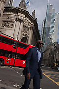 Just as a red Routemaster bus turns the corner, a businessman of colour wearing dark sunglasses walks along Bishopsgate street on 12th September, in the heart of the capitals financial centre, the City of London, UK.
