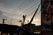 A man stands at the top of a tall ladder and works on the electricity line at sunset in Cox Bazar, Chittagong Division, Bangladesh, Asia.